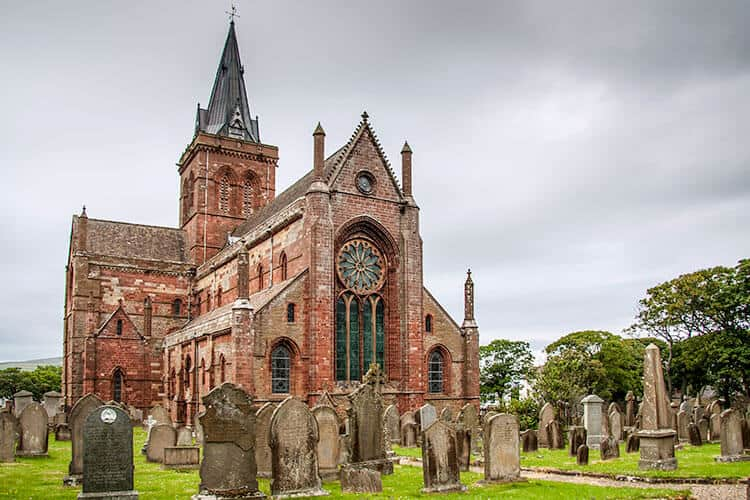 St. Magnus Cathedral in Orkney with old weathered gravestones in front of the towering red/brown cathedral