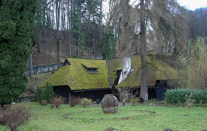 A mossy building on the grassy grounds below Bran Castle. A Large boulder sits in the ground in front of the medieval moss covered building. If you are searching for Dracula at Bran Castle in Transylvania start here!