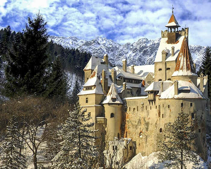 Medieval Bran Castle nestled in a thick forest of snow covered trees with it's red roof tops covered in a thin layer of snow. The Carpathian Mountains are behind the castle with a bright blue sky filled with white fluffy clouds.