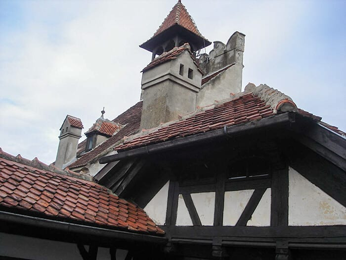 Roof top of Bran Castle, White weathered walls with rusty red roof tiles