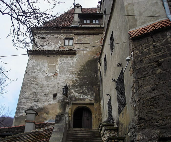 The entrance to Bran Castle, medieval walls stained with age. Off white stone walls with a rusty red roof top. Romanian writing is engraved into the rock above the brown wooded doors.
