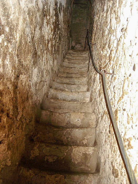 Creepy worn stairs leading up to darkness inside Bran Castle