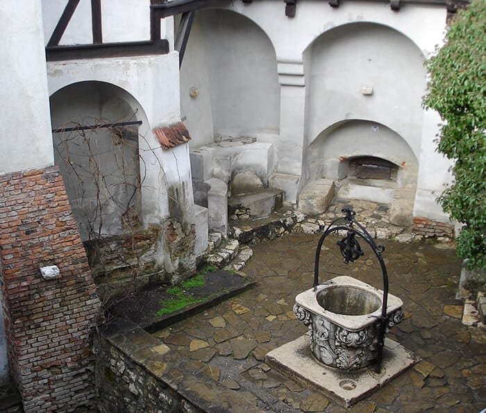 A white weathered well sitting in the center of Bran Castle walls