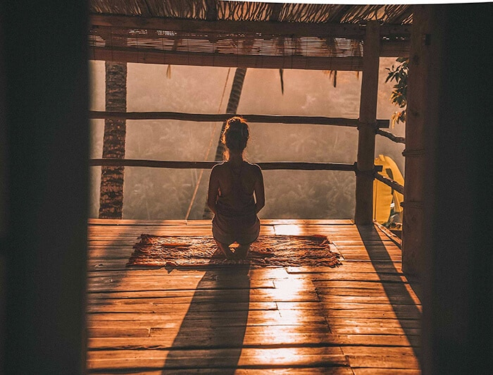Woman meditating and doing yoga looking out into the forest of Bali
