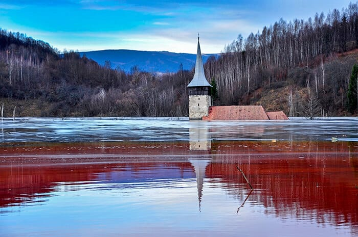 Church Steeple sticking out of red lake of toxins in Geamana Romania. Spooky and haunted Romania location.