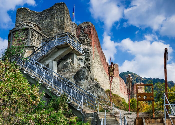 Poenari Castle from the side, stairs leading up to the castle, next to the stairs are two men impaled on large sticks like the Romanian leader Vlad the Impaler used to do to his enemies. Spooky and haunted Romania location.