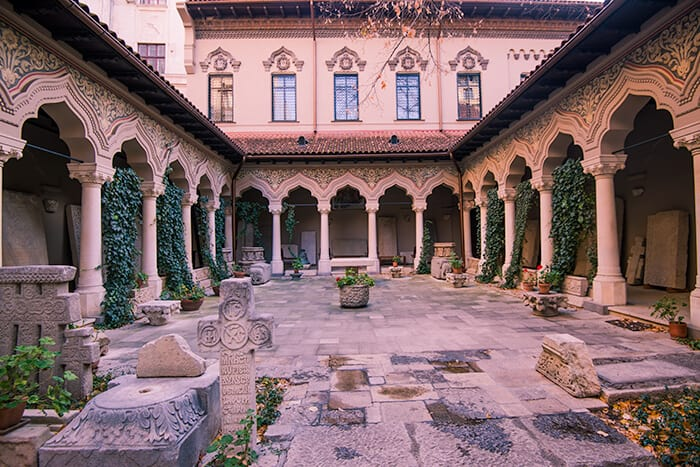 The court yard of Stavropoleos Church in Romania with arched pathways on either side. Spooky and haunted Romania location.