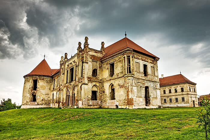 Banffy Castle in Romania - Abandoned Castle, ruins in the middle of a field, aged walls, empty windows with a red roof. Spooky and haunted Romania location.