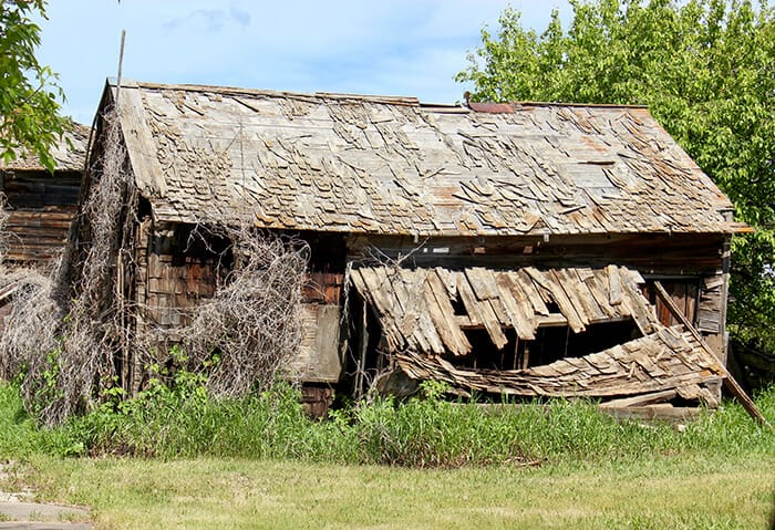 Wooden barn falling apart, hole in the smaller attached roof that looks like a monsters face