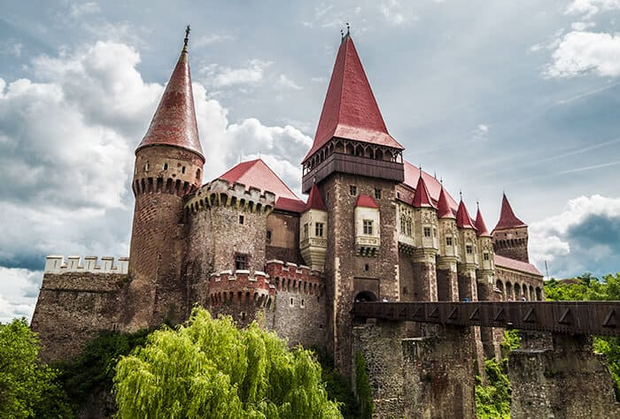 Striking Corvin Castle in Romania with tall walls, a bridge leading into the castle and red tiled roof. Spooky and haunted Romania location.
