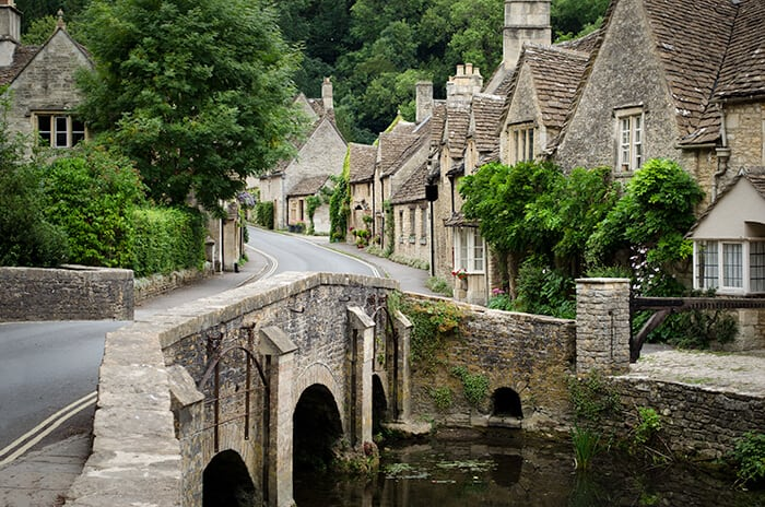 Quaint village in the Cotswolds in England. Picturesque brick road over a water way leading to British stone houses lined with ivy.