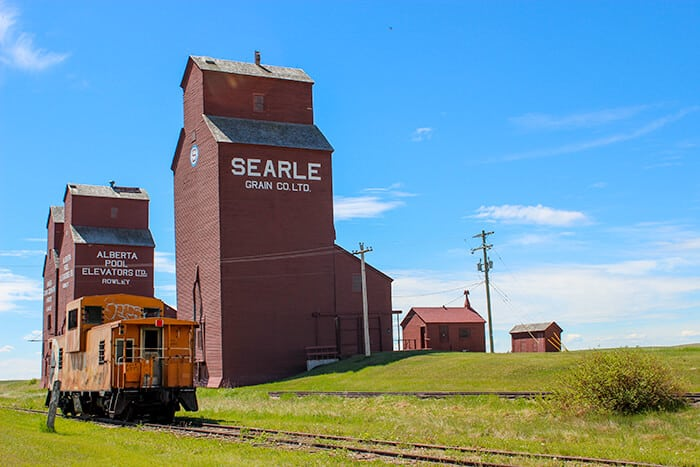 Three Red/Brown Grain Elevators and an abandoned orange train car with graffiti sitting on the tracks in front of the elevators in Rowley Alberta