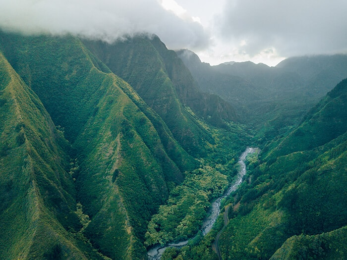 Lush green mountains with a stream of water flowing through in Hawaii