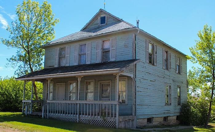 Historic former hospital in the ghost town of Rowley Alberta. Huge blue house with the paint wearing off from being weather worn and abandoned. Windows are all boarded up from inside the house with wood.