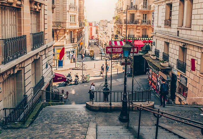 Stairs leading to the street - full of people and cafes in Montmarte, Paris in France.