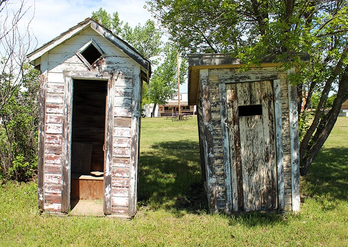 Two run down wooden outhouses sitting in the grass. Paint is scraping off showing how weathered and aged the outhouses are.