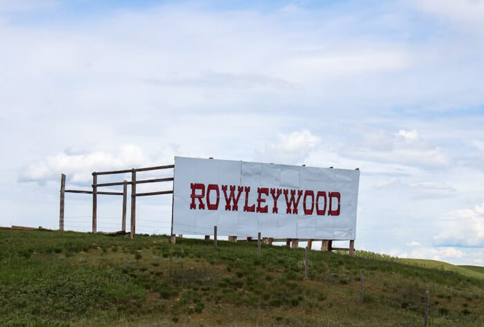 Rowleywood - Large white sign with ROWLEYWOOD written in red letters on a grassy hill next to the highway leading to the ghost town of Rowley