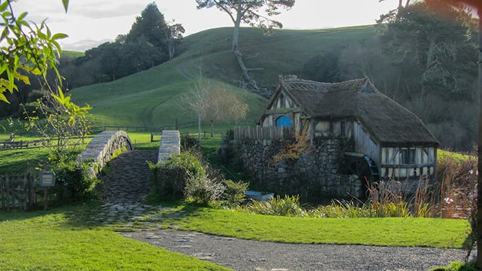 A tiny hobbit house in the lush green grass with a dirt path with a bridge over a small stream in The Shire in New Zealand
