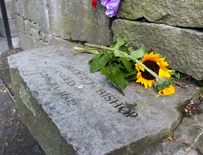 At the Salem Witch Trials Memorial by the Old Burying Point Cemetery Bridget Bishop memorial bench at the Salem Witch Trials Memorial. Stone bench with Bridget Bishop Hanged engraved on the stone. There are several bunches of yellow sunflowers sitting on top of her stone.