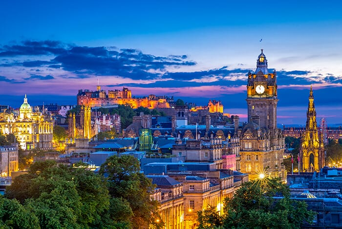 Edinburgh City Scape at dusk, blue and pink sky with buildings lit up. A tower clock on the right side with the Edinburgh Castle in the back. One of the places a foreigner can get a job in Scotland.