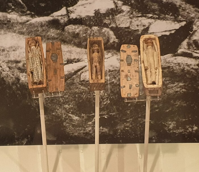 Tiny wooden coffins containing tiny dolls made of wood.