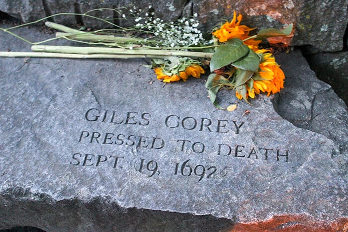 Stone bench with the engraving Giles Corey Pressed to Death Sept 19 1692. Above the engraving is a bunch of orange and yellow sunflowers honoring Giles memory. Salem Witch Trials Memorial.