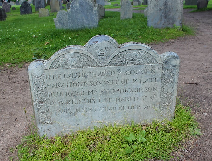 The Old Burying Point Cemetery is a Large thin headstone with an engraving of a skull at the top in the center of the stone. The gravestone is for Mary Higginson.