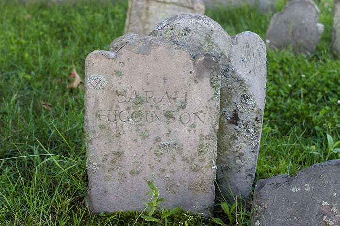 At the Old Burying Point Cemetery Small gravestone with the name Sarah Higginson engraved with a slightly larger headstone right behind Sarahs gravestone.