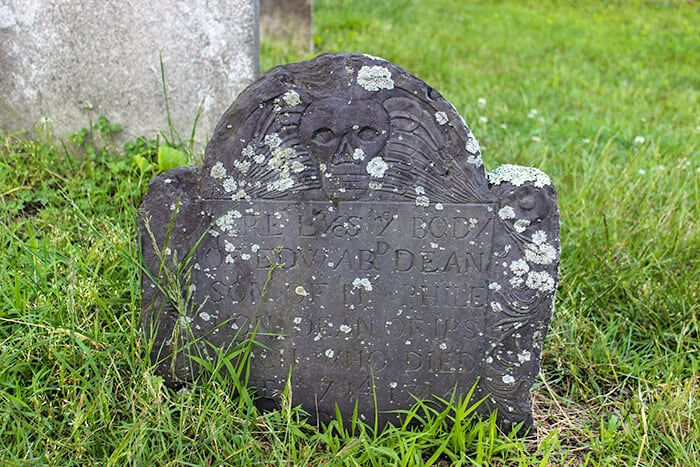 In the Old Burying Point Cemetery is a dark head stone of a grave, the stone has an engraving of a skull with weathered white marks in various places on the stone.