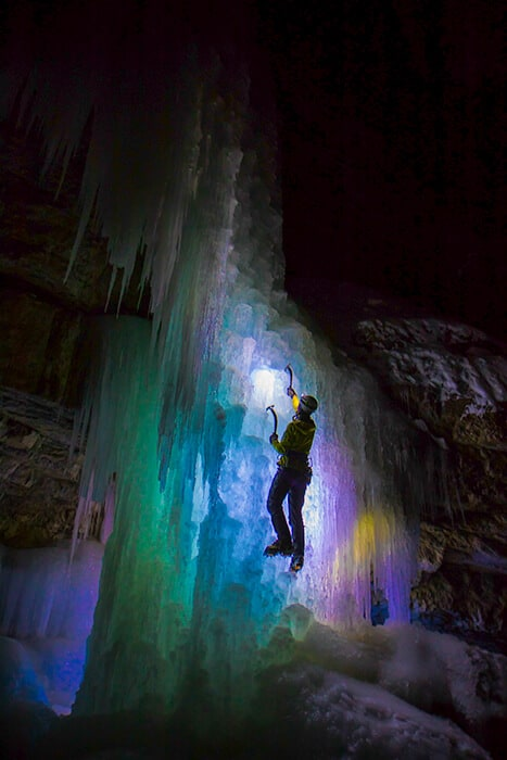 Man climbing ice with ice picks and cleats in Jasper National Park at night in the winter. Rainbow color lights shine up the icicles from behind the frozen waterfall.