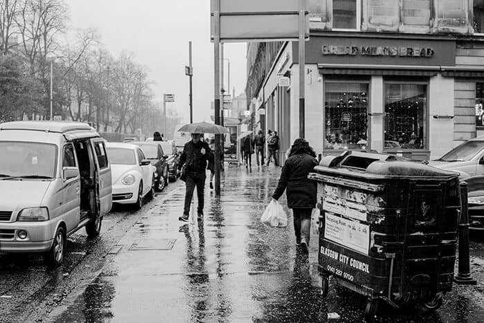 Black and White Photo of a rainy street in Glasgow. Rubbish Bin on the right side of the photo with several people walking on the pavement carrying umbrellas.