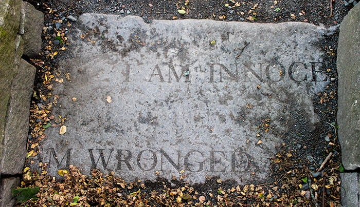 Salem Witch Trials Memorial Witch Quotes located just outside the Old Burying Point. The cement has I AM WRONGED and I AM INNOCENT written.
