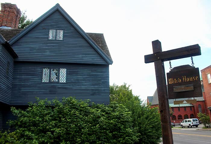Exterior of the Witch House with a wooden sign with gold lettering saying The Witch House in Salem