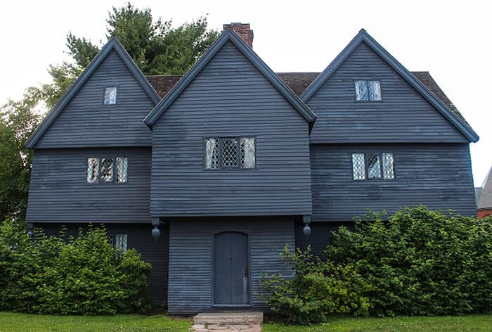 The front exterior of The Witch House in Salem Massachusetts. The house is black with a roof that is three gables and a brick chimney in the center of the house.