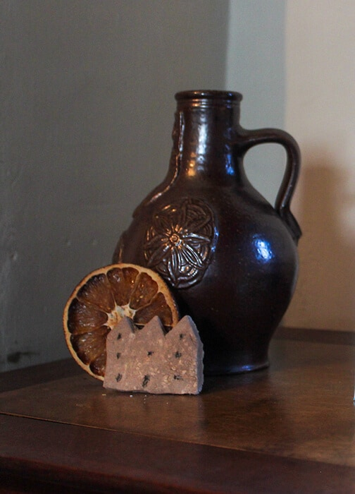 A small clay bottle with a dried orange slice sitting in front of it