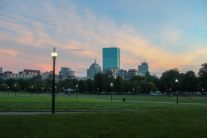 Boston Common at dusk, green field with skyscraper skyline in the background
