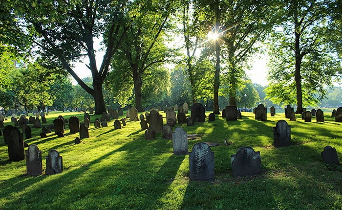 Central Burying Ground in Boston. Old cemetery with old weathered tombstones randomly placed on a grassy hill.
