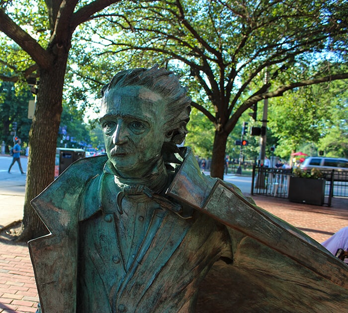Green statue of Edgar Allan Poe in Boston from the waist up.