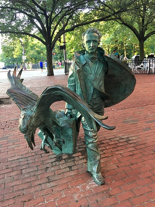 Full statue of Edgar Allan Poe in Boston. The statue of Edgar and his open briefcase with a huge raven bursting out.