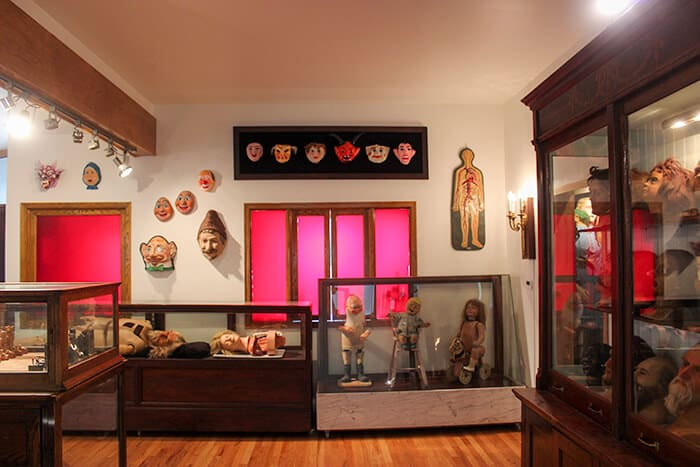 Inside the Museum of Fear and Wonder - dolls in cases, wax heads on display to the right and old halloween masks from the 1930s hung on the wall