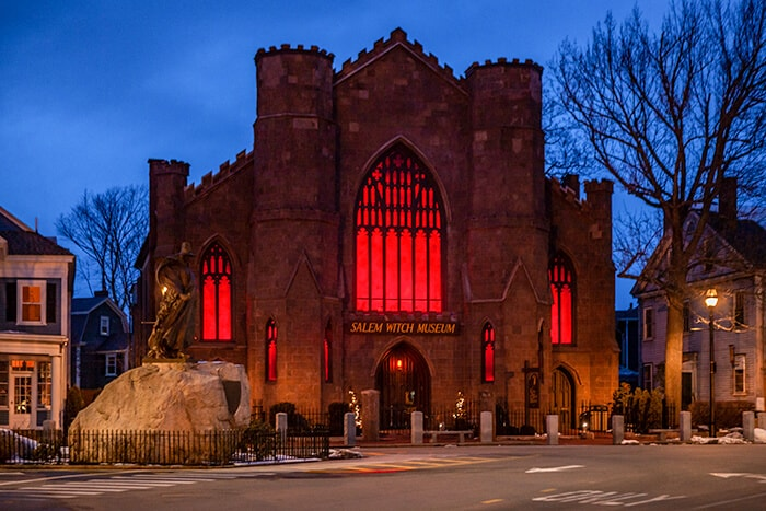 Salem Witch Museum at night, castle like building with large windows lit up with a red light. Learn about the History of The Salem Witch Trials here.