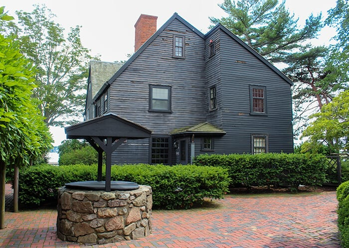 The side of the House of the Seven Gables in Salem Massachusetts. The house is a dark brown/black with a small well made out of stones to the left of the house.