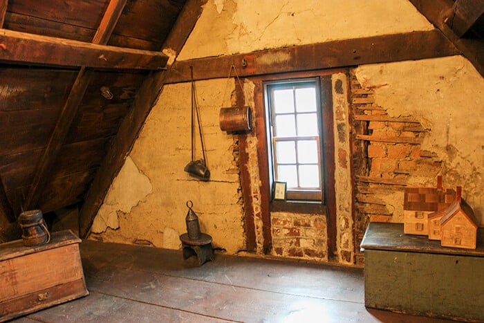 Inside the House of the Seven Gables in Salem - The attic with obvious signs of construction. A few items such as an oil lamp hang on the walls from a hook.