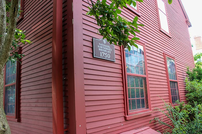 "A red wooden house with a sign that says ""The Birthplace of Nathaniel Hawthorne 1750"""