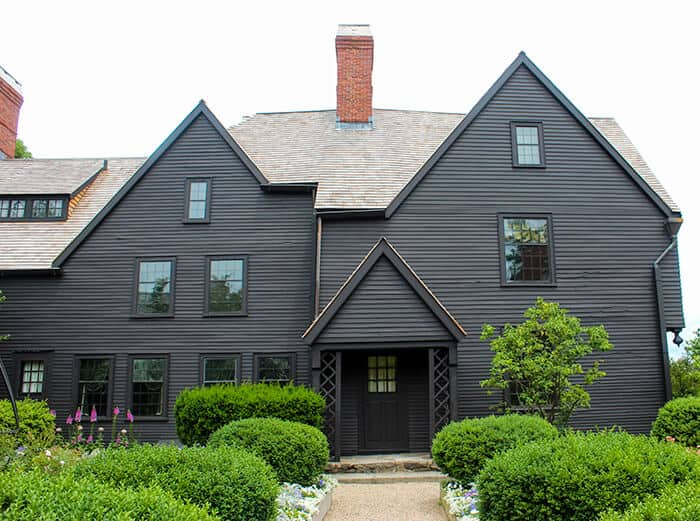 The front of a large mansion known as the House of the Seven Gables in Salem Massachusetts, painted dark brown/black with three gables and a chimney in the center. There is a path leading to the front door with green bushes on either side.