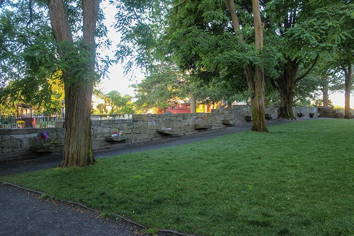 The Witch Trials Memorial in Salem where the history of the Salem Witch Trials is remembered. Several granite benches are placed along a granite wall with two trees in the foreground