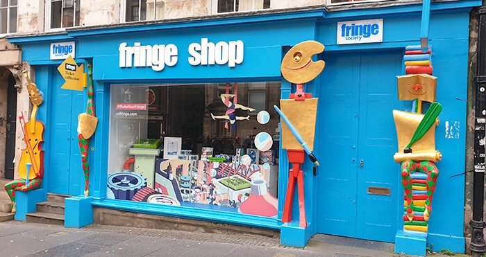 Bright blue store front of the Edinburgh Fringe Shop on the Royal Mile