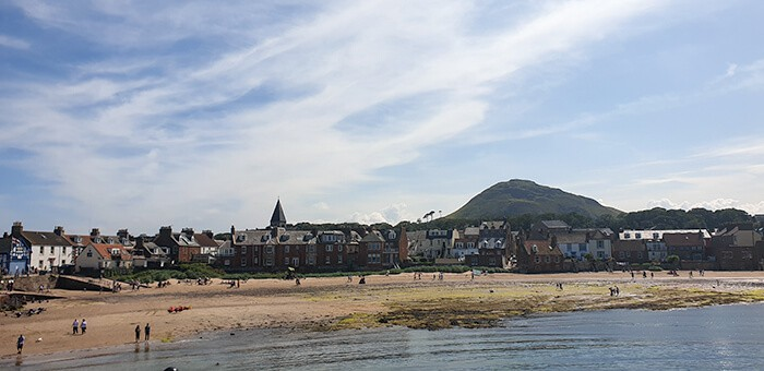 View of the beach side town of North Berwick in Scotland, beach with the townsite and a large hill.