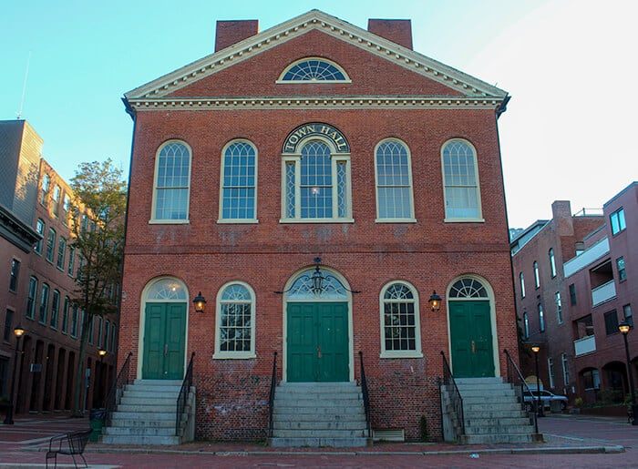 Old Town Hall in haunted Salem MA - brick buidling three green doors and stairs leading up to each door