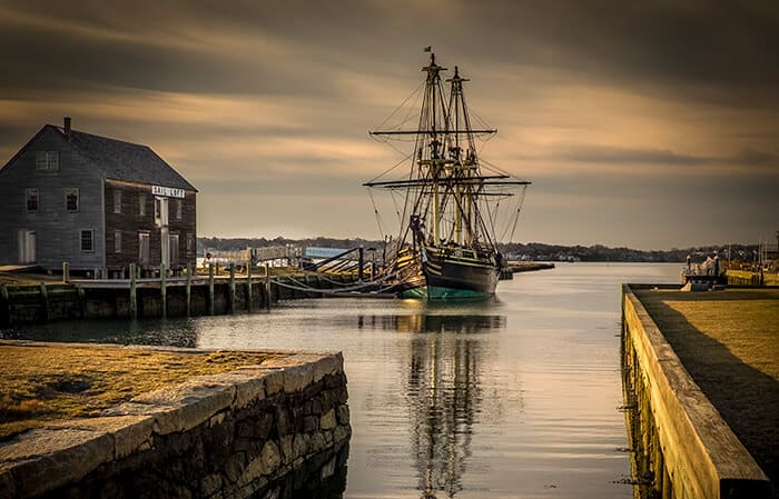 Salem Port at dusk, large ship docked next to old wooden building on the water